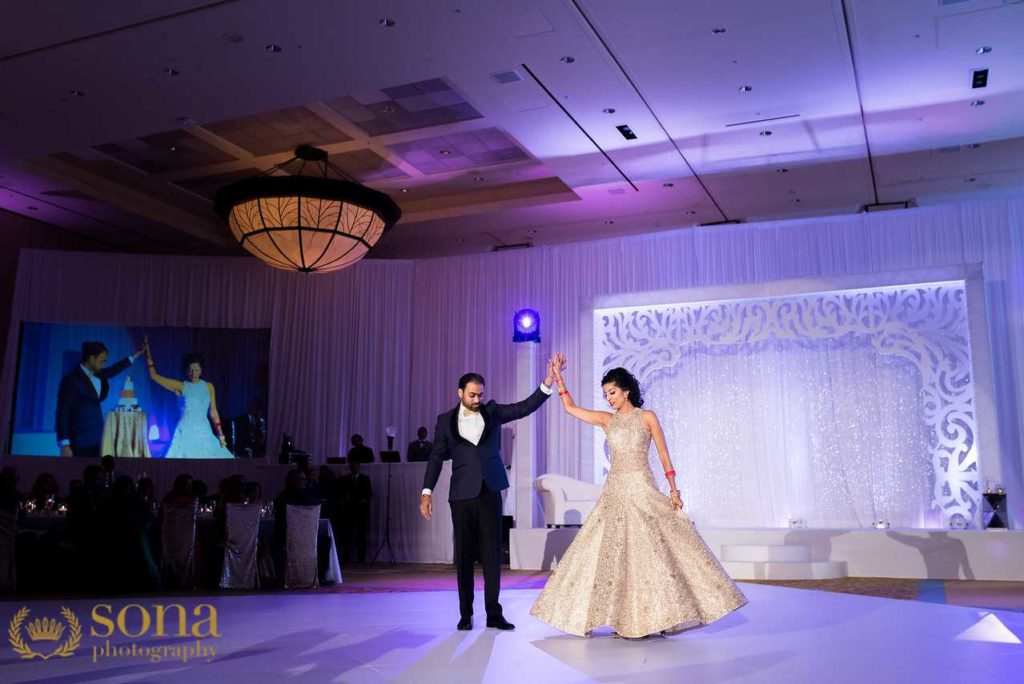 Beautiful Indian bride in a sparkly gown being twirled by her groom