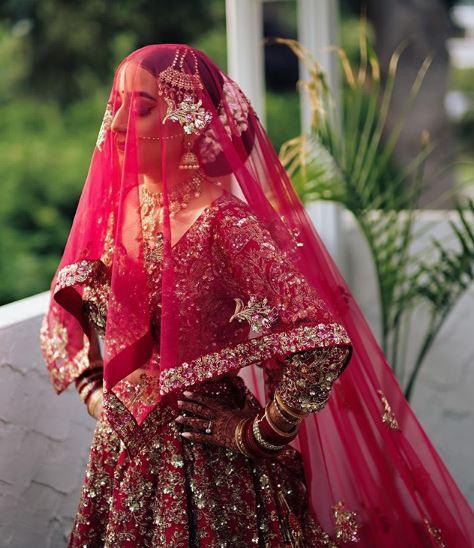 Indian bride wearing red net dupatta and intricate deep red wedding lehnga