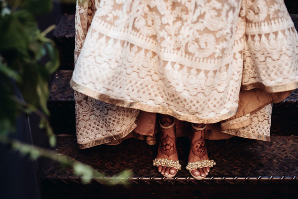 Bride lifting her pink lehnga to show off mehndi covered feet