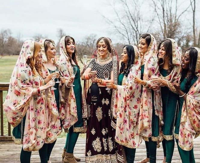 Bridesmaids in green suits and floral dupattas