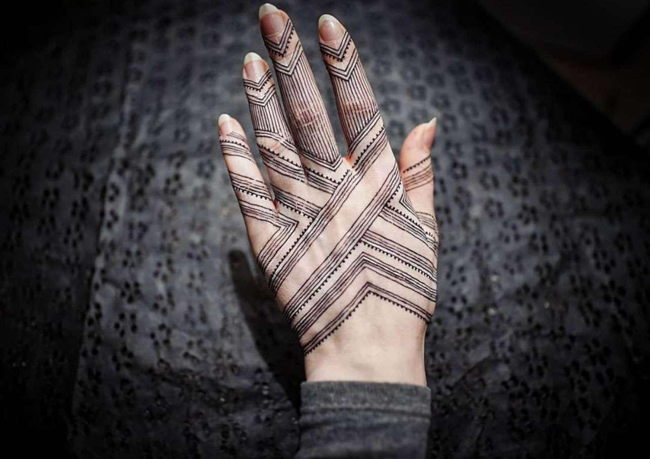 Hand over dark background with criss cross minimal mehndi line design
