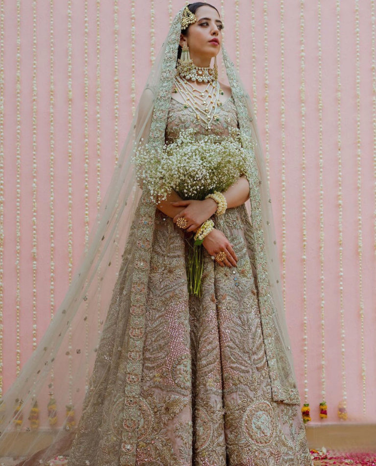 Woman posing in ornate bridal lehnga with baby's breath bouquet