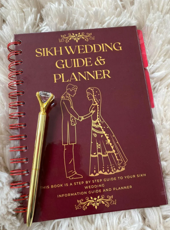 Red and gold Sikh wedding planner with gold pen on top